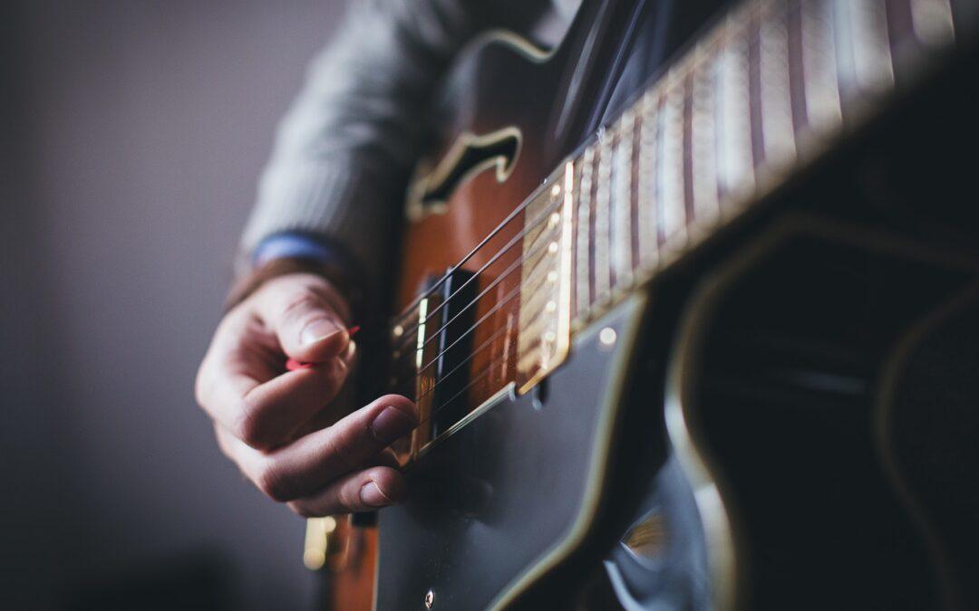 Anschlaghand mit Plektrum eines Gitarristen mit E-Gitarre.